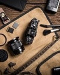 photography gear on wooden table, digital camera lens and other accessories.
